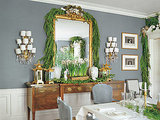 A lush garland draped over a gilt mirror creates a glam dining room space. I love the ivory, gold, and green color scheme. Source