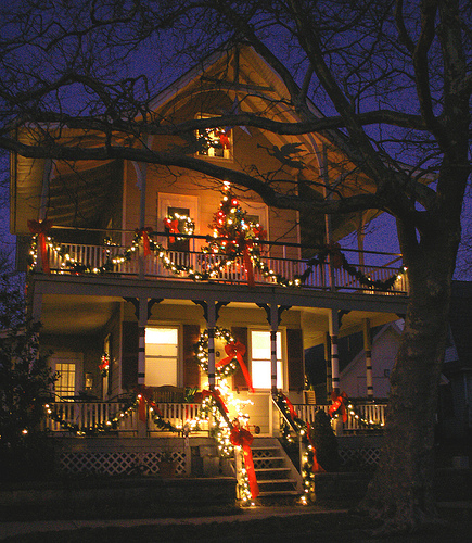 Those of you who have two porches can go wild with your decorations, adding coordinating lights and garlands to both floors.  Source: Flickr User Sister 72