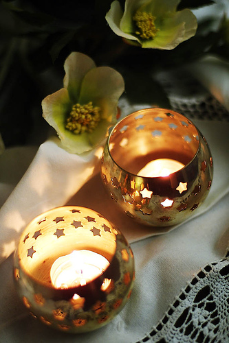 Star votives are a subtle reminder of the holiday, while delicate vintage linens and scattered petals really add romance to this holiday table.  Source:  Flickr User Usama Ochida