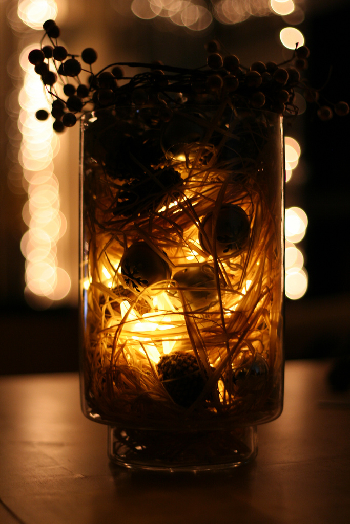 Fill an empty glass vase with some small ornaments, strands of raffia, acorns, and some LED holiday lights, and top it all off with some holly. Source: Flickr User Spy on Pea