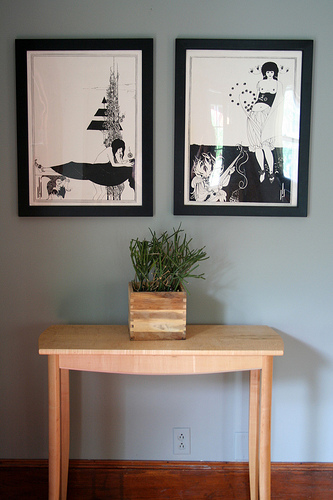 Pen and ink artwork are anchored by a simple table.