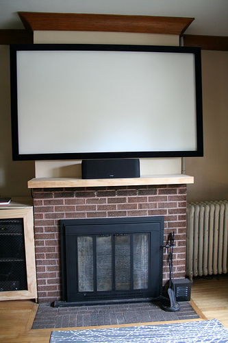 A projector screen dominates the fireplace, while a built-in shelving unit on the left, made by the owners, will soon have a matching unit on the right, with shelves topping both, to frame the screen.