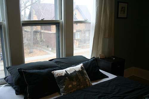 Instead of a headboard, a window overlooking the quiet street frames the bed.