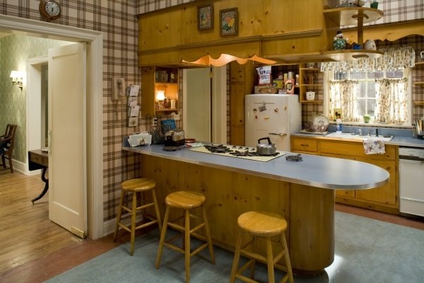 The Drapers' kitchen embodies the early '60s aesthetic. From the plaid(!) wallpaper to the knotty-wood cabinets, it captures the era. Source