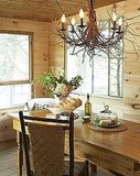 An organically shaped branch chandelier, knotty wood walls and ceilings, and woven-backed chair give this dining room a woodsy, cozy feel. Source