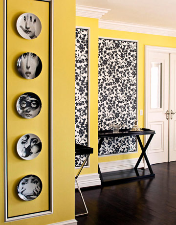 Even design icon Max Azria loves the look of hanging plates. At his house, he chose Fornasetti plates to grace his yellow walls. The black-and-white patterns really pop against the wall color.  Source