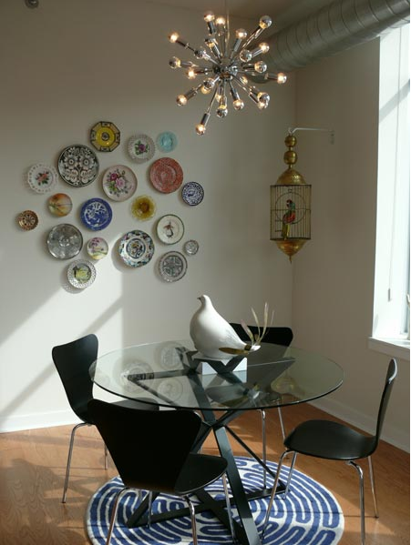 "While some may call plate decorating ""grandma style,"" this home proves that modern and classic elements can blend perfectly in a space. The classic look of hung plates looks great with the modern chandelier and chairs.  Source"