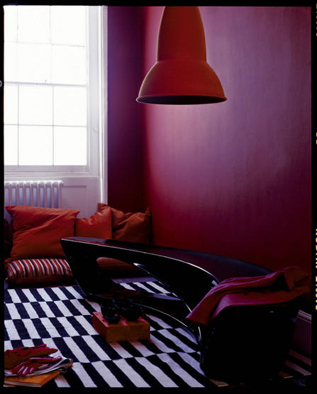 This moody pink wall is given depth thanks to the orange pendant shade and deep orange cushions. I also love the graphic punch of the striped cotton rugs.  Source