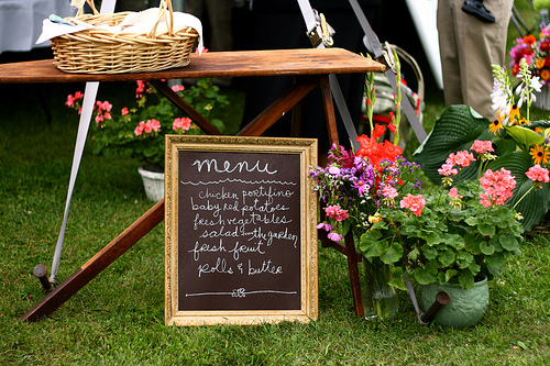 The wedding menu was written on a gilt-framed blackboard, and a basket of treats was placed on a vintage wooden ironing board. The effect is utterly charming.