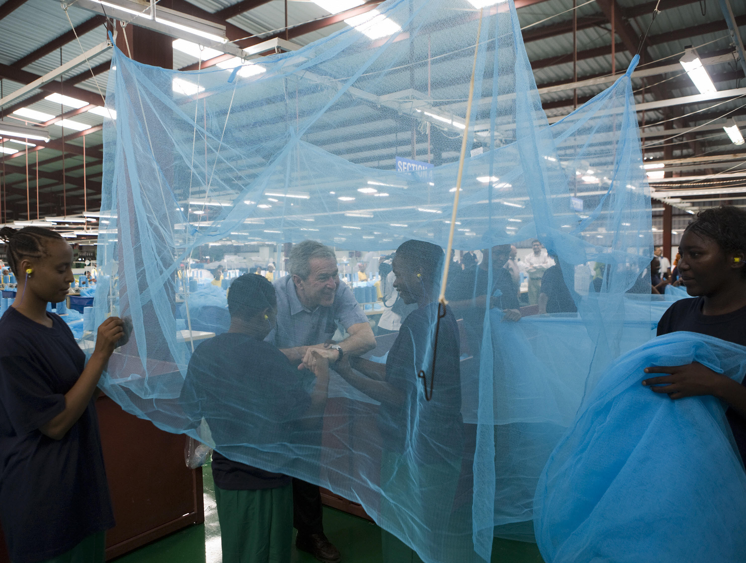 Bush greets workers under a mosquito bed net in Tanzania.