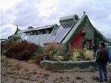 Here's a view of the house with solar hot water panels, passive solar windows, and a curved adobe garden wall.Source