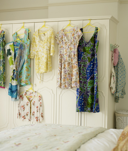 "Another image in Lake's portfolio features beautiful blue and green floral dresses on unifying yellow hangers, used to garnish the doors of a plain, white closet. In her book, Bazaar Style, with words by Joanna Simmons, alongside a similar image, it reads: ""Clothes can become art when carefully hung across a wall. Here, a collection of dresses and skirts, made by the fashion-designer owner of this house, lines one wall. If you display clothes this way, take them down regularly for a brush and shake out, to remove dust and prevent creases."" She later writes, ""Hanging a beautiful dress or colorful hats and bags from closet doors or a coat rail is an easy way to bring pattern and vibrancy to a sleeping space."" Source"