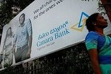 A woman in Bangalore, India, stands next to a very Western looking billboard.