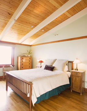 High, beamed ceilings in the master bedroom imbue the room with an airy feel.