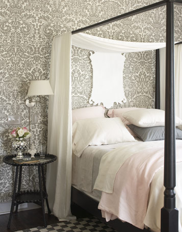 A checkerboard floor, damask-patterned wallpaper, and four-poster bed are a few of the highlights of the bedroom.