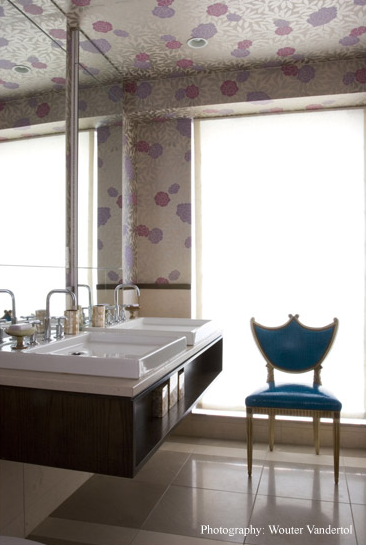 In the bathroom, whimsical wallpaper travels from the wall to the ceiling, while a turquoise chair adds a touch of solemnity to the room.
