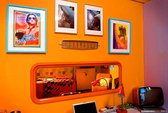 A bedroom mirror looks more like a rear view car mirror than any standard home decorating fare. Framed posters evoke '60s rock poster psychedelia.