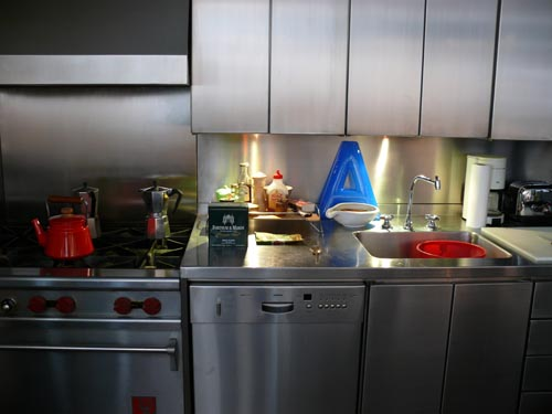 Pops of color are introduced into this stainless-steel kitchen with a red teapot and oven knobs, as well as a blue A, for Allen.