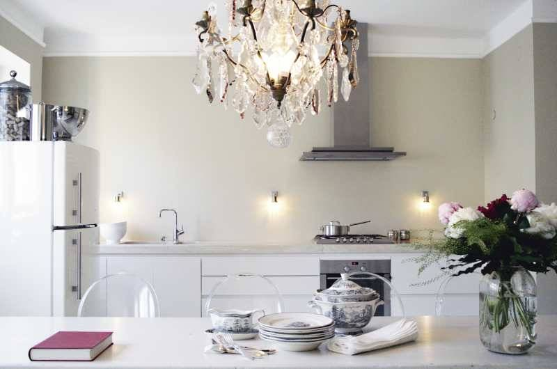 An antique chandelier is a glamorous contrast to the modernity of this kitchen.