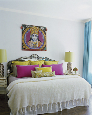 The master bedroom shines with a mirrored headboard and plenty of colorful, ethnic textiles.