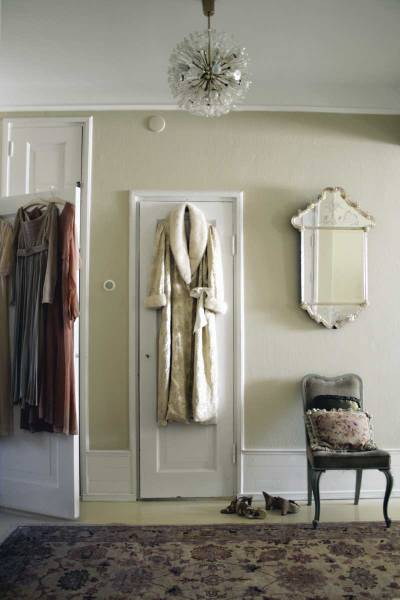 A vintage dressing gown serves as a decorative touch. A Venetian mirror and mid-century chandelier appear again. The traditional oriental rug is a nice contrast to the modernity of the chandelier.