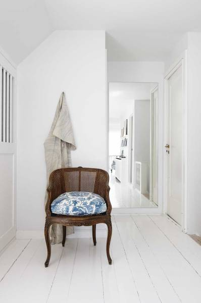 An antique chair is dressed with a cushion in the same delft-esque textile as used in the bedroom, creating a running theme throughout the house.