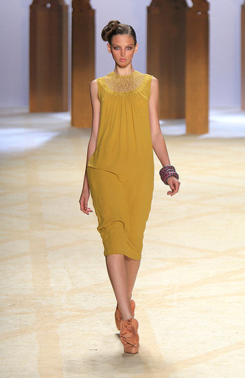 This rich yellow dress has beautiful movement in the body, and its detailed neckline draws the eye up.