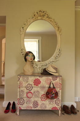 A dresser painted in soft florals beside an ornate mirror makes this dressing area super femme.
