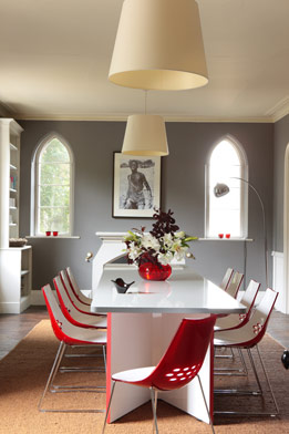 Arched windows are an original feature of this former vicarage. Oversize lampshades play tricks with scale.
