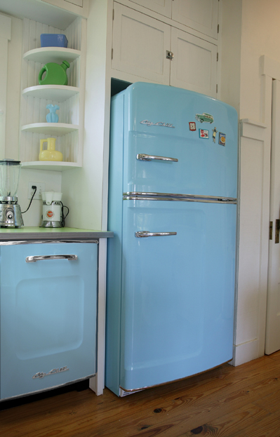 The bright pops of baby blue in the big Chill fridge and matching dishwasher are complemented by the displayed ceramics, and the white cupboards let the tones shine.