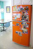 A retro kitchen gets a relaxed look with an orange Big Chill that's swathed in family photos.