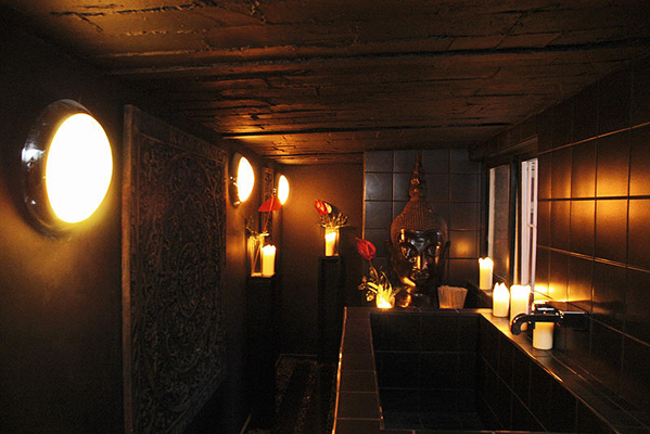 A deep, trough-like sink and a collection of candles give this bathroom a hotel-like aura.