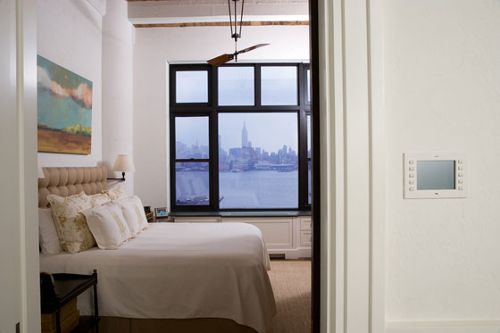 The bedroom is serene and understated, with white walls and unfussy bedding, leaving the attention to the beautiful landscape that hangs above the bed and the one glaring from the window.