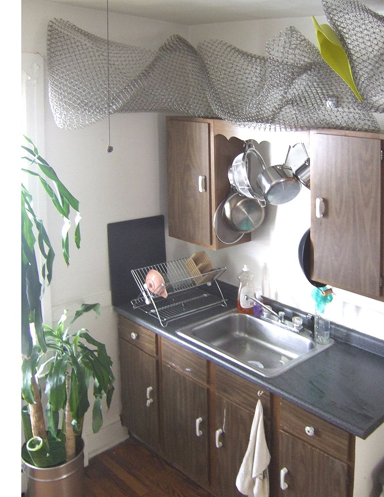 In the kitchen, wire mesh is sculpted to hold pots, pans, and other household objects.