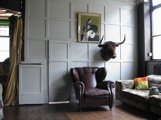 A well-loved brown leather chair and some taxidermy create a masculine reading nook.