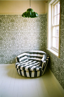 Black-and-white stripes smartly temper this busy wallpaper.