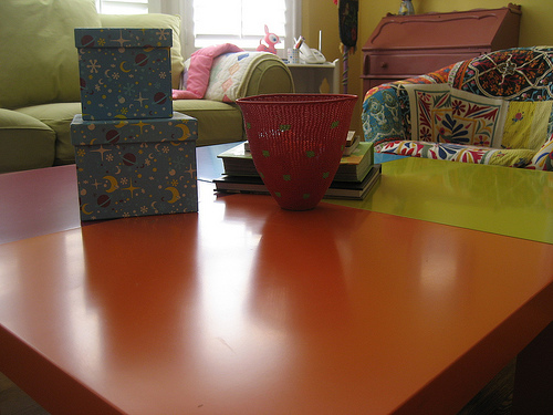 Four brightly colored Ikea tables are joined together to make a large coffee table in the living room.
