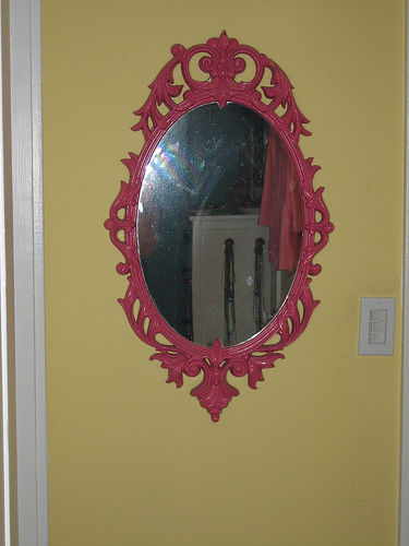 Across from the art piece, a vibrant pink mirror catches the light.