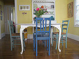 A graceful white dining table is surrounded by mismatched yet complementary chairs in shades of blue.