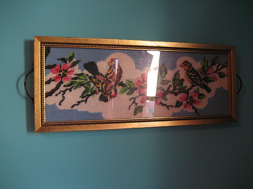 An embroidered bird wall hanging adds a vintage touch.