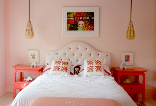 In a girl's bedroom, the Blythe Avenue C print ($125) hangs above the bed, looking down at a big-eyed doll resting on the pillows. A pair of coral Hollywood Regency side tables flanks the bed.