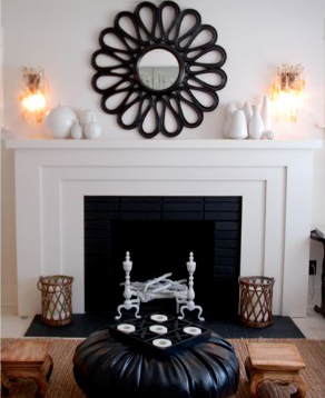 A bold black sunburst mirror is the focal point in this fireside sitting area, reflected by a round black leather pouf.