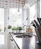 Herbs soak up sunlight in the kitchen window, and shades with a teacup pattern add subtle style.