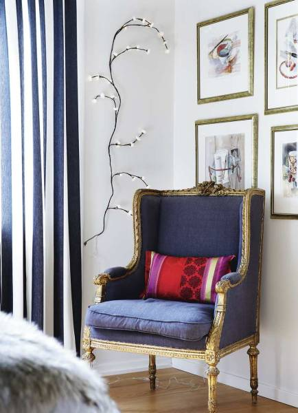 An antique French Bergère chair is modernized with a colorful pillow.
