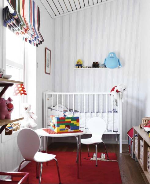 In the white-walled nursery, color is added with striped curtains, a red rug, and a well-loved collection of toys.