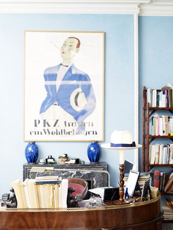 Rounded furniture, blue ceramic vases, and baby blue paint create an elegant work space.