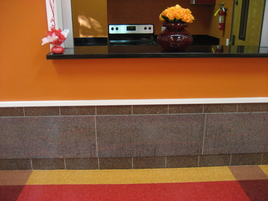 The tile work on the wall is a great accompaniment with the vibrant flooring.