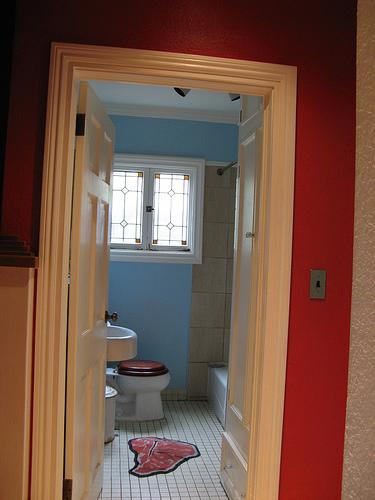 The bathroom's cool blue walls are offset by the red steak mat.