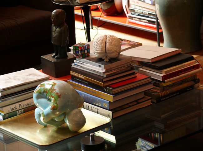 Stacks of books topped with art figurines create an artistic display on the coffee table.
