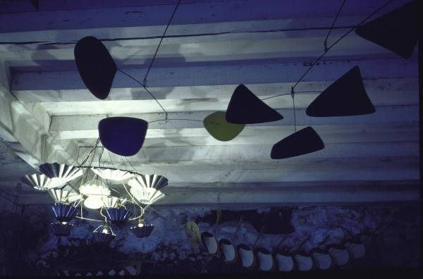 Some of Calder's mobiles dance across the wooden-beamed ceiling.